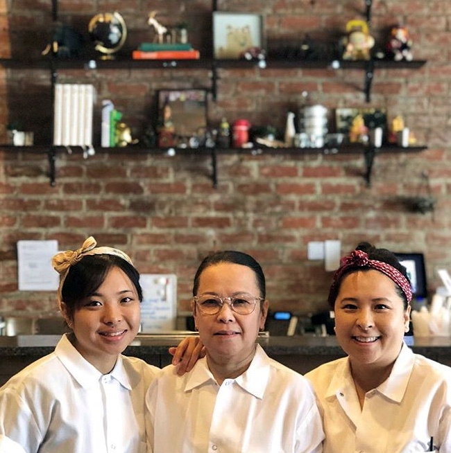three generations of the Asapahu family, Grandmother, mother and daughter, pose in the dining room of their family restaurant, Ayara Thai
