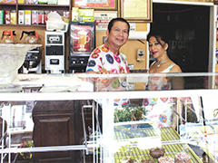 Glady Uy, left, owner of Super Donut House in Hollywood behind the counter of his Hollywood business