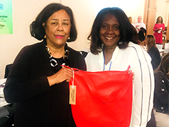 EWDD General Manager Jan Perry, left, poses with handbag designer Lavena and one of her products, a red leather handbag, at the FWPO Build Your Business event
