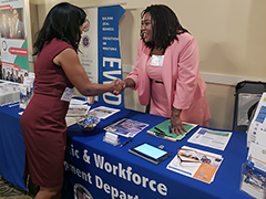 EWDD Business Response Unit staff Vanessa Willis (right) greets a visitor at the LAWA Business Connections event