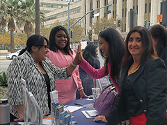 (left) EWDD Assistant Chief Grants Administrator Jackie Rodriguez and EWDD Senior Project Coordinator Vanessa Willis assist female small business owners at LA's Women's Entrepreneurship Day