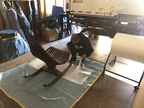 A Box Pack & Ship employee packages an antique chair for shipping