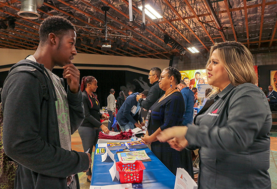 A job seeker (left) at the Southeast Los Angeles WorkSource Center job fair May 2, 2019 speaks with Virginia Montano (right), a representative from truck driver services company ProDrivers