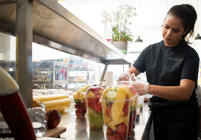 Lupita's daughter Luz Arango cuts up fresh fruit for customers