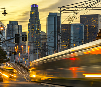 vehicle and light rail transportation in downtown Los Angeles at dusk