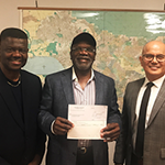 Dr. Dotun Oyenuga (center) proudly holds a check toward a $250,000 SBA loan that will allow his firm to fulfill a contract to with Metro